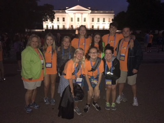 Night-time group photo in front of the White House